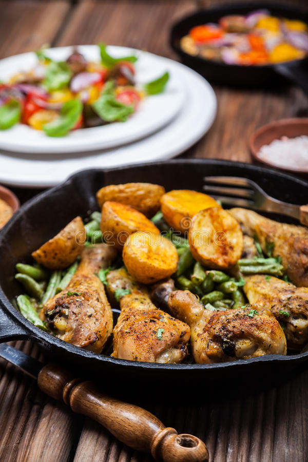 Chicken legs in pan with potatoes and salad royalty free stock photos