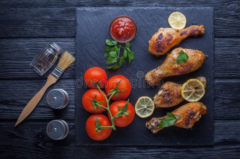 Chicken legs with tomatoes, lemon, parsley and ketchup on a black slate board. Grilled chicken legs with tomatoes, lemon, parsley and ketchup on a black slate royalty free stock photo