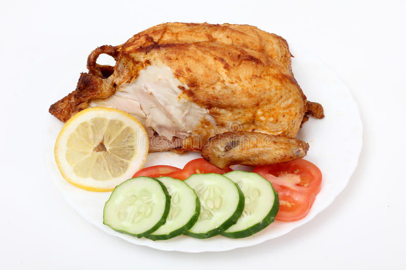Chicken and lemons. Color photo of fried chicken on a plate stock photography