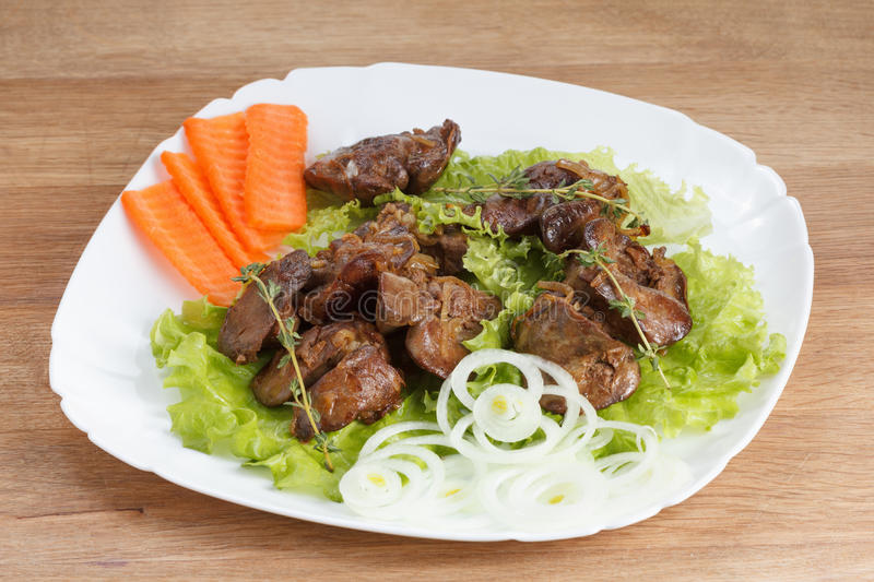 Chicken liver cooked with onions, lettuce and spices royalty free stock photos