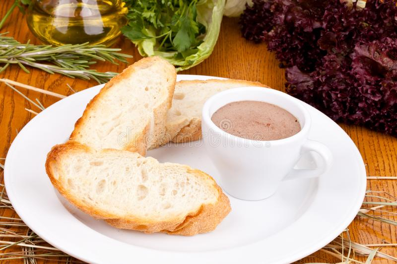 Chicken liver pate in cup and sliced baguette on white plate. Close up stock image