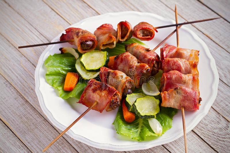 Chicken liver wrapped with bacon on skewers. Grilled liver kebabs with vegetables on white plate. stock photo