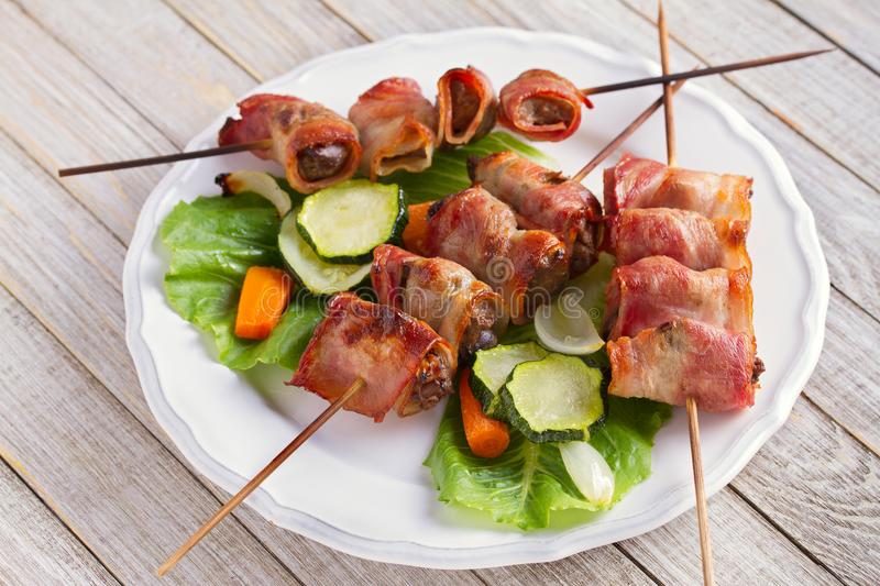Chicken liver wrapped with bacon on skewers. Grilled liver kebabs with vegetables. royalty free stock images