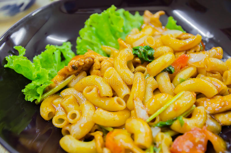 Chicken macaroni. On black plate royalty free stock images