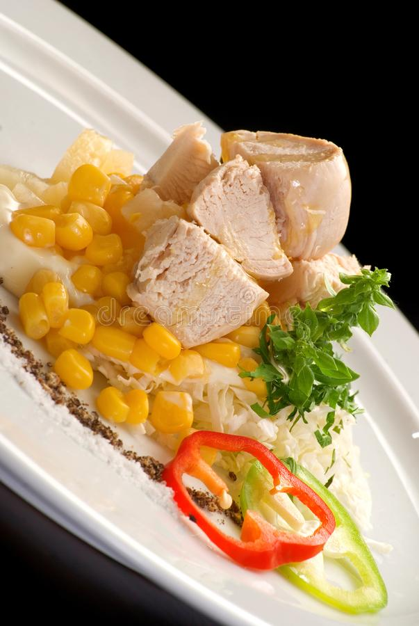 Chicken meat with corn, bell pepper, mayonnaise and sauces on a white plate royalty free stock photo
