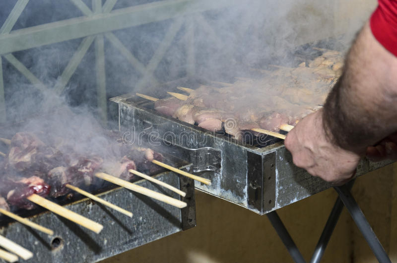 Chicken and meat skewers on the grill and hand man royalty free stock photography