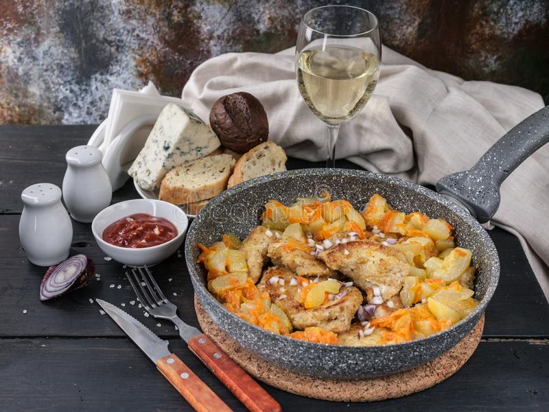 Chicken meat with stewed curry with vegetables in a pan, cheese, bread and white wine. Horizontal shot stock photo
