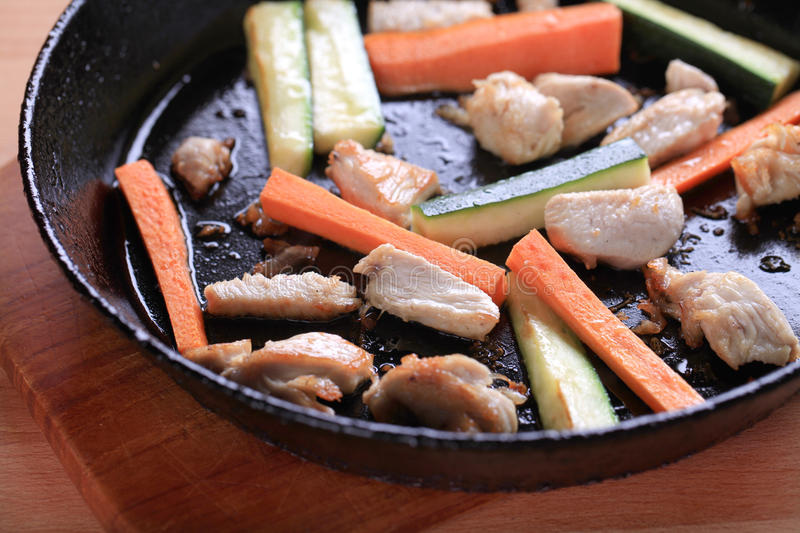 Chicken meat and vegetables on a pan royalty free stock images