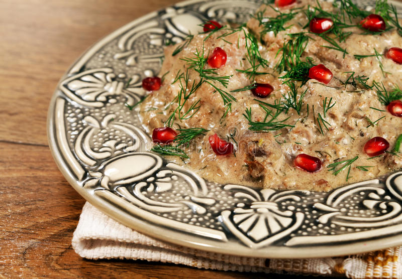 Chicken meat with walnuts, locale food of Georgia. Hot a dish of ethnic cuisine of Georgia prepared from chicken meat and walnuts with pomegranate royalty free stock photos
