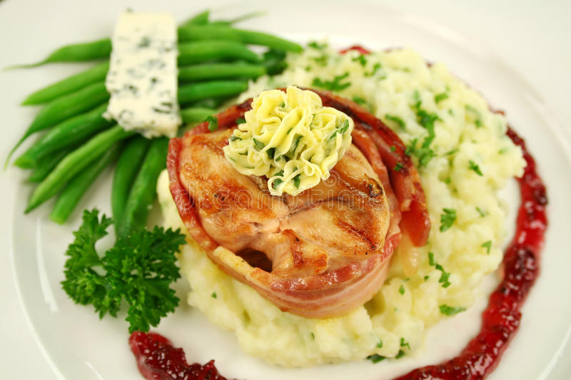 Chicken Mignon. Chicken fillet mignon on parsley mashed potato with green beans and blue cheese stock images