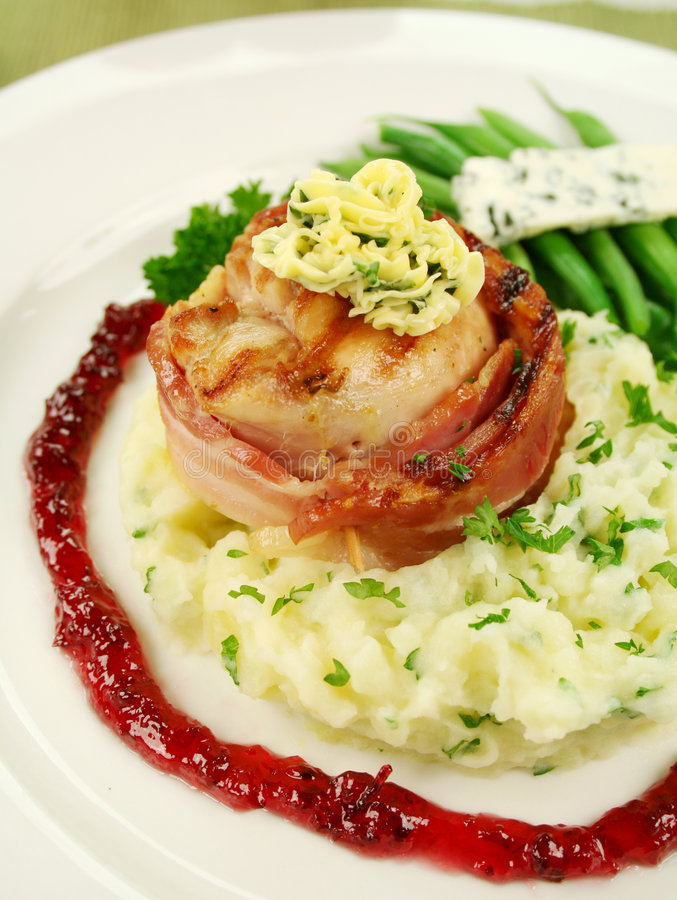 Chicken Mignon. Chicken fillet mignon on parsley mashed potato with green beans and blue cheese and red wine and raspberry jus royalty free stock photography