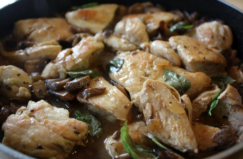 Chicken with Mushrooms and Basil. Chicken cooked with mushrooms and basil in a skillet stock photos