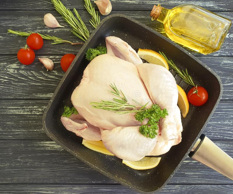 Chicken fraw whole cuisine dinner gourmet diet cuisine ingredient a frying pan on a white wooden background, tomato, lemon. Chicken natural raw fresh whole in a royalty free stock images