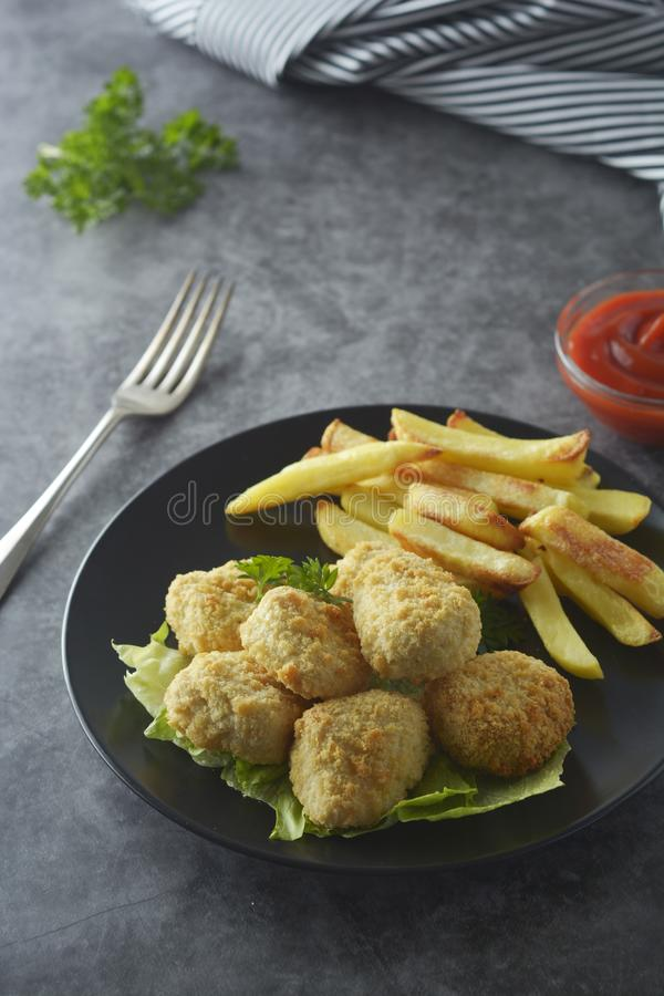 Chicken nuggets with french fries on dark background, top view royalty free stock photos