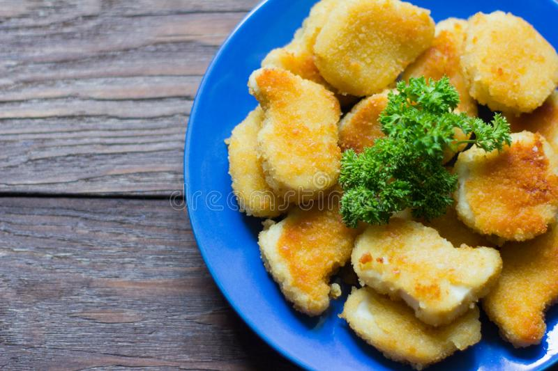 Chicken nuggets fried to Golden brown with parsley on wooden background stock images