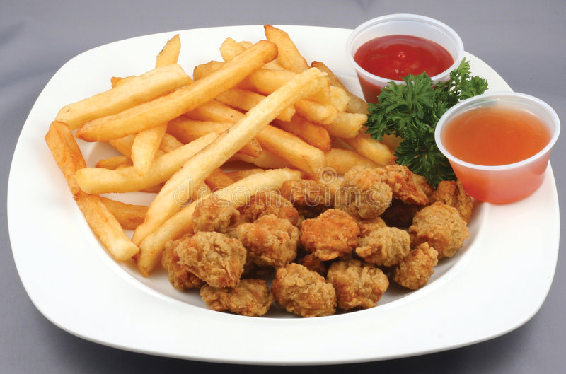 Chicken nuggets and fries. Chicken nugget lunch with fries, ketchup and a dipping sauce stock photography