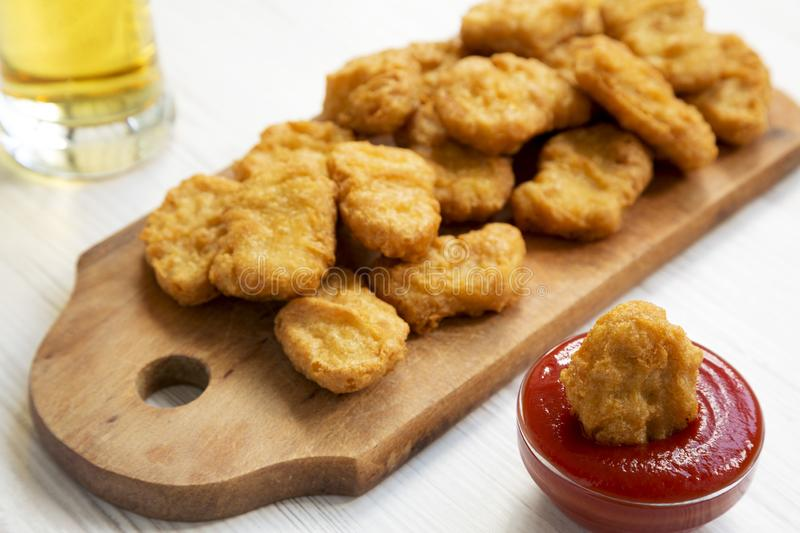 Chicken nuggets with ketchup and glass of cold beer on a white wooden background, low angle view. Closeup.  stock image
