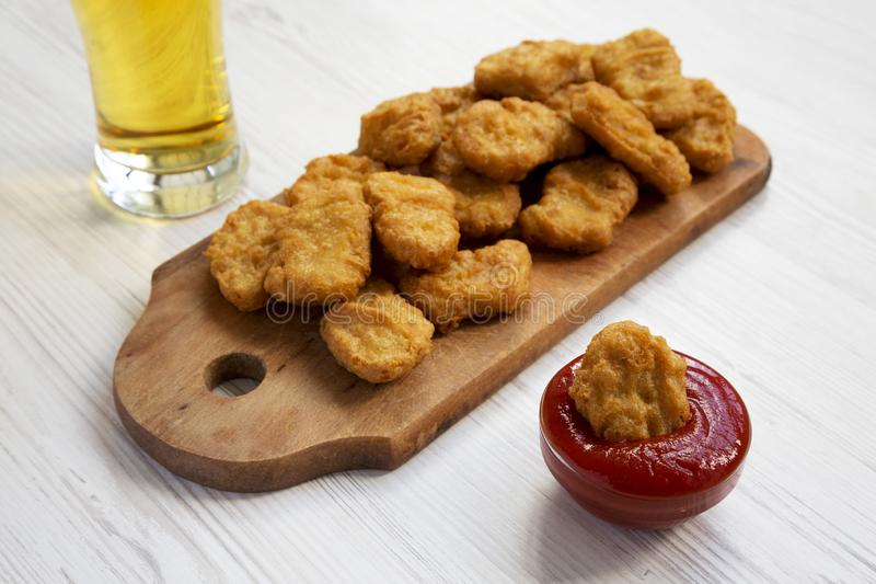 Chicken nuggets with ketchup and glass of cold beer on a white wooden background, low angle view. Closeup.  royalty free stock photos