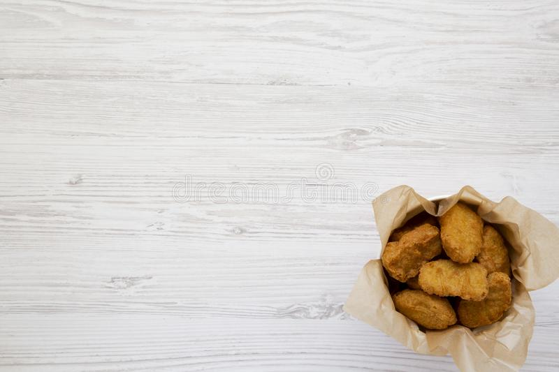 Chicken nuggets in a paper box over white wooden surface. Overhead, from above, flat lay. Copy space.  royalty free stock photography