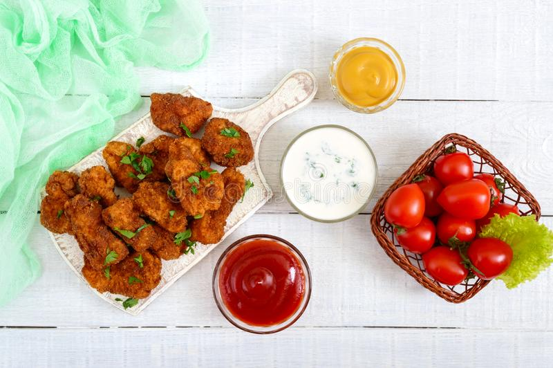 Chicken nuggets. Pieces of deep-fried crispy meat, on paper with different sauces stock images