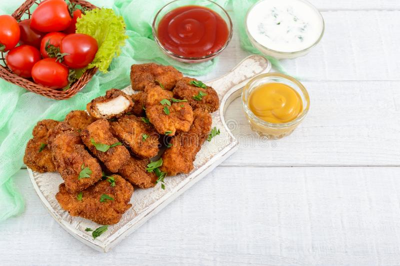 Chicken nuggets. Pieces of deep-fried crispy meat, on paper with different sauces stock photos