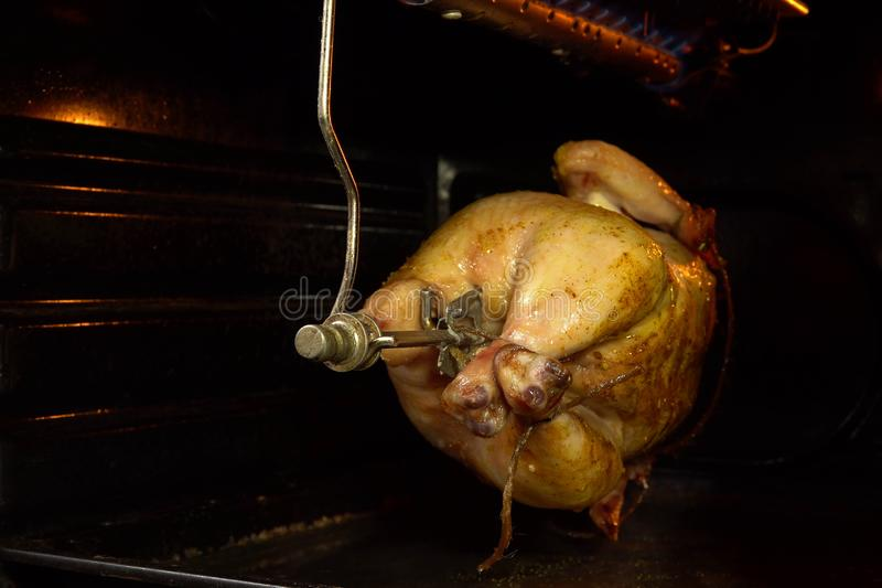 The chicken in the oven roasting on a skewer stock photography