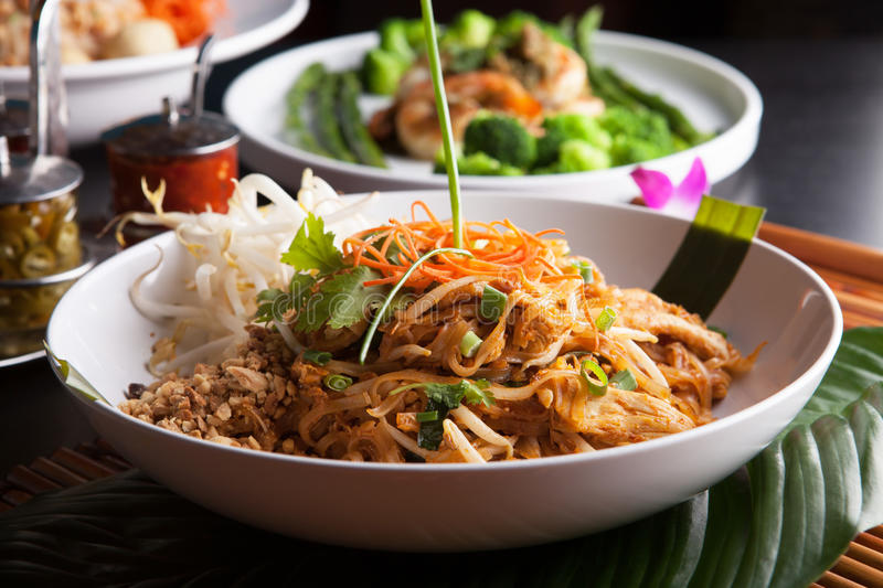 Chicken Pad Thai Closeup. Chicken pad Thai with a variety of other fine Thai food dishes. Shallow depth of field stock photos