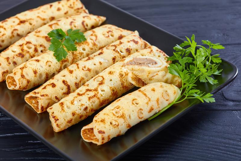 Chicken pate stuffed Crepes on plate. Delicious Homemade chicken pate stuffed Crepes on black plate decorated with fresh parsley leaves, view from above, close stock photos