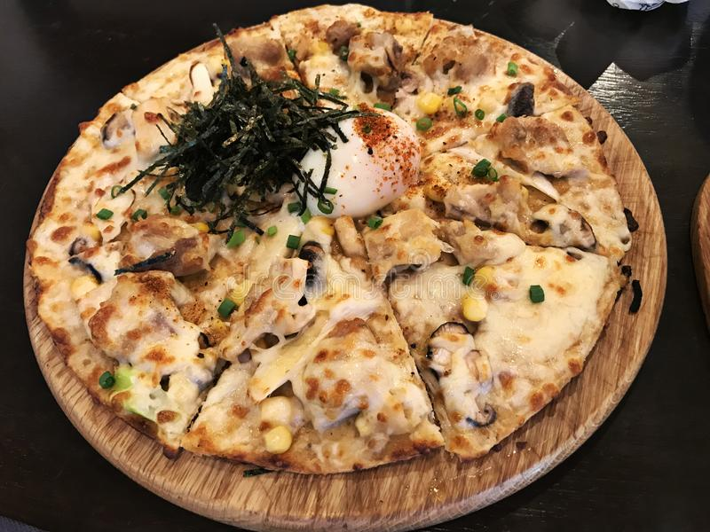 Chicken Pizza topped with soft-boiled egg and dried seaweed. Chicken Pizza topped with soft-boiled egg and dried seaweed in Thailand stock image