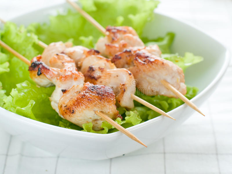 Chicken (or pork) on a grill spit. With lettuce stock image