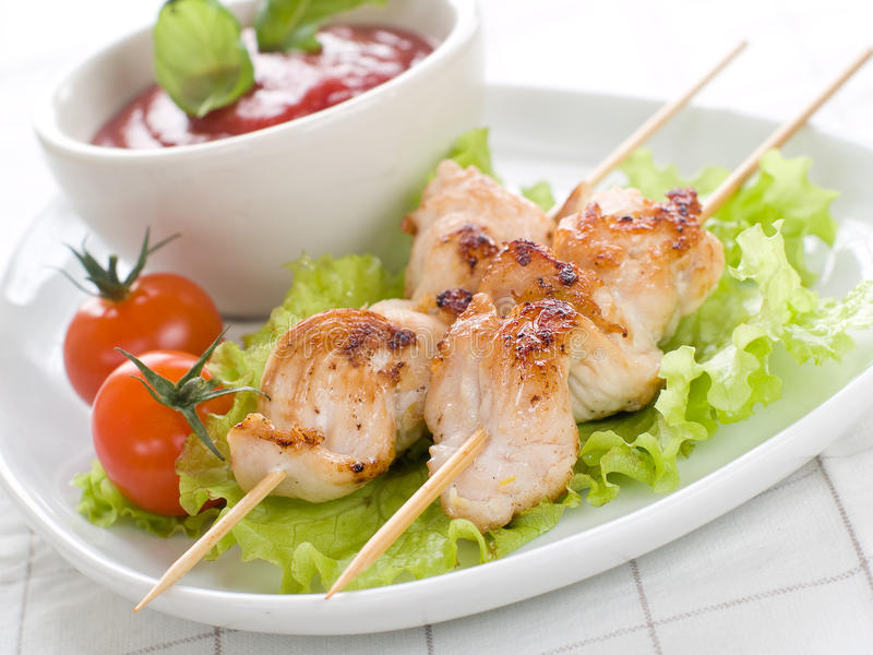 Chicken (or pork) on a grill spit. With salad and bowl of ketchup stock image