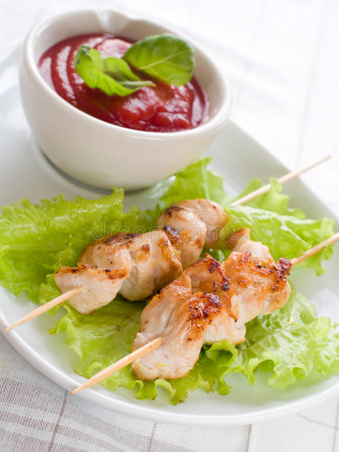 Chicken (or pork) on a grill spit. With salad and bowl of ketchup royalty free stock photo