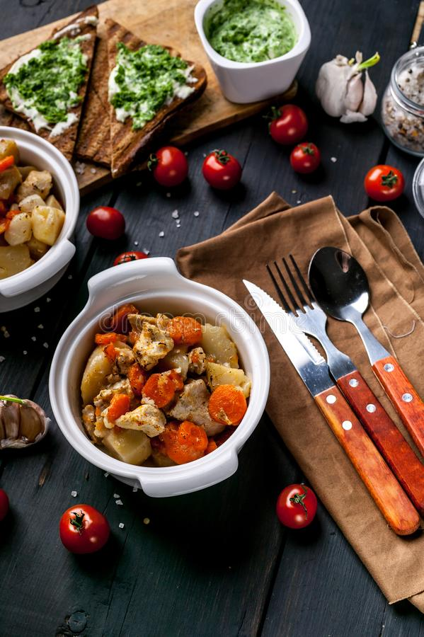 Chicken with potatoes and carrots, sandwich with cheese and cherry tomatoes on a dark wooden background. Vertical shot stock image
