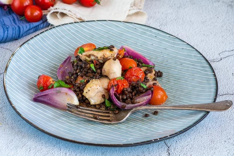 Chicken, puy lentils and cherry tomatoes bake. Chicken and cherry tomatoes bake with puy lentils royalty free stock image