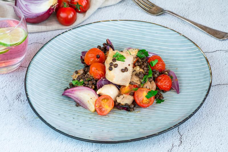 Chicken, puy lentils and cherry tomatoes bake. Chicken and cherry tomatoes bake with puy lentils stock image