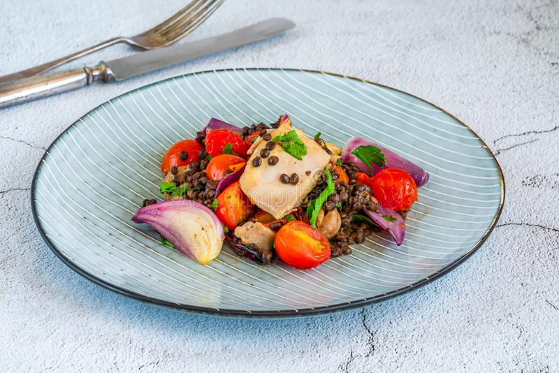 Chicken, puy lentils and cherry tomatoes bake. Chicken and cherry tomatoes bake with puy lentils royalty free stock photography