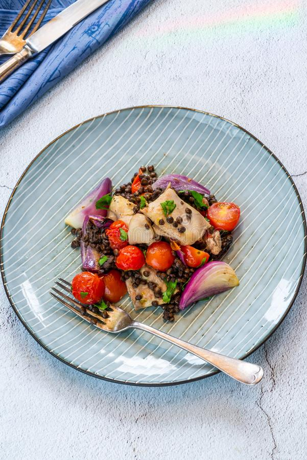 Chicken, puy lentils and cherry tomatoes bake. Chicken and cherry tomatoes bake with puy lentils - high angle view stock image