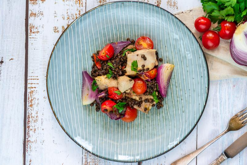 Chicken, puy lentils and cherry tomatoes bake. Chicken and cherry tomatoes bake with puy lentils - top view royalty free stock images