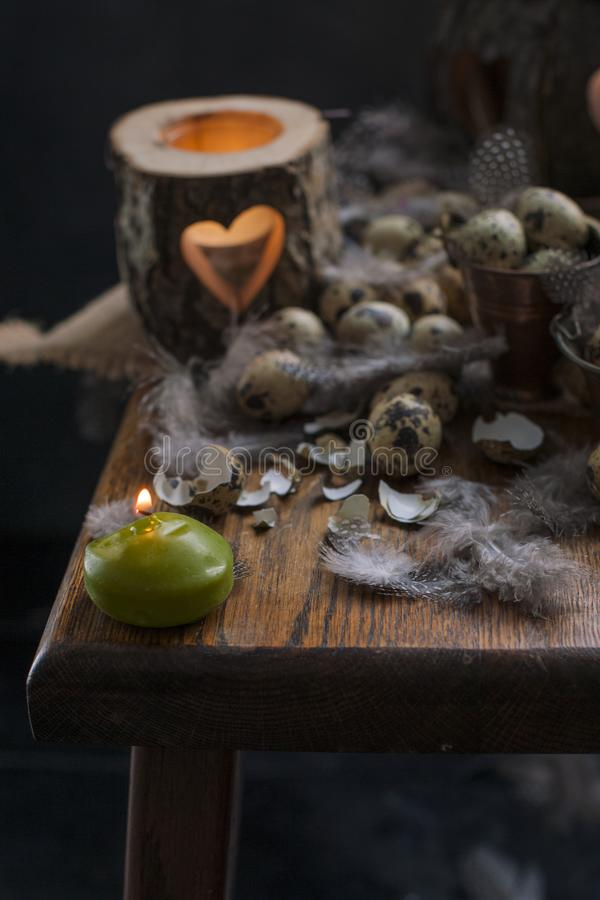 Chicken quail eggs, candles and tree branches, feathers and decor for Easter. Copy space royalty free stock images