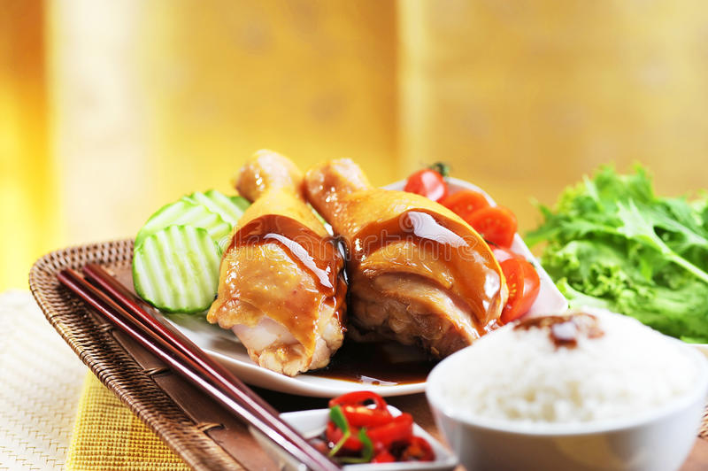 Chicken rice with oyster sauce, cucumber and lettuce on tray stock image