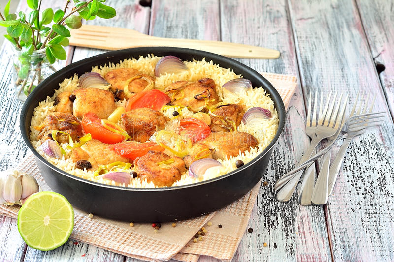 Chicken with rice and vegetables in a frying pan spices stock images