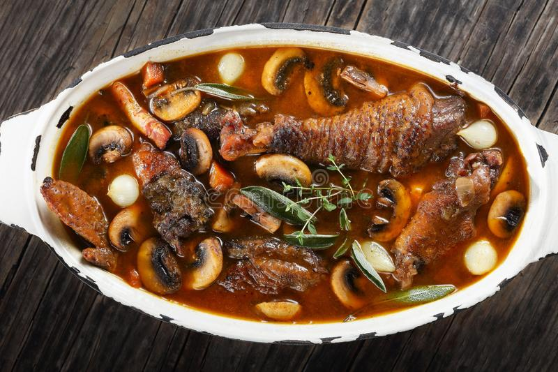 A chicken rooster stewed in red wine. Festive dinner recipe - a chicken rooster stewed in red wine with spice, herbs, authentic french recipe - coq au vin In a royalty free stock photo