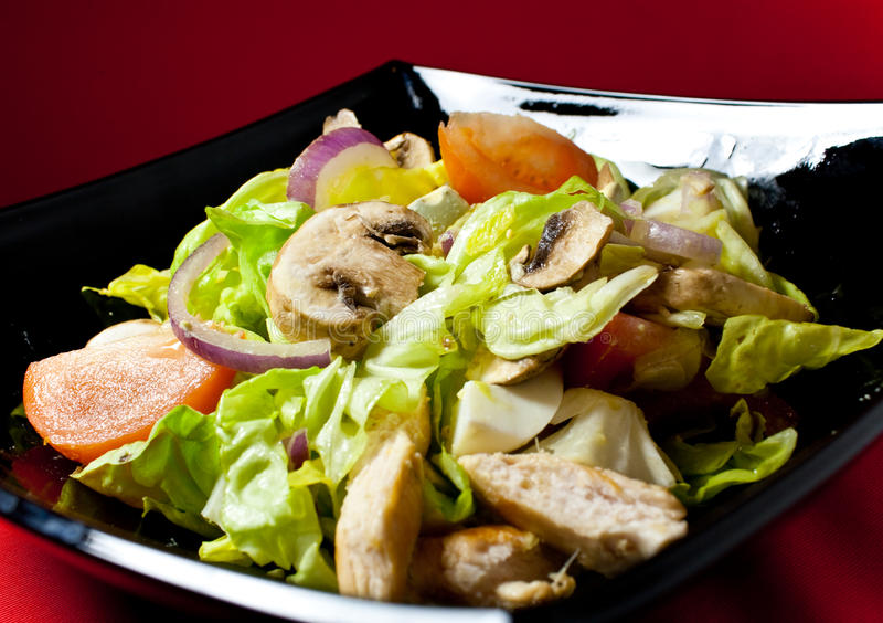 Chicken salad. With mushroomsin black bowl royalty free stock photography