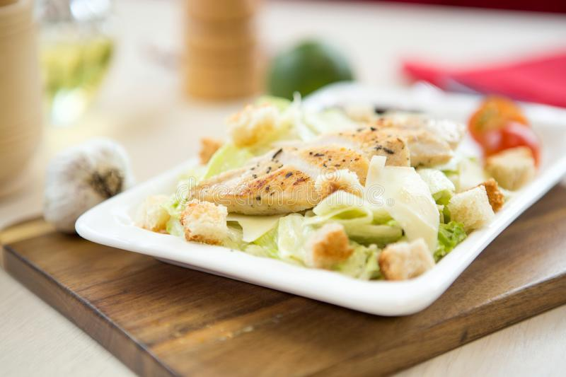 Chicken salad with cherry tomatoes, black olives, kidney bean, sweet corn, cucumber and ice lettuce. Close up royalty free stock photo