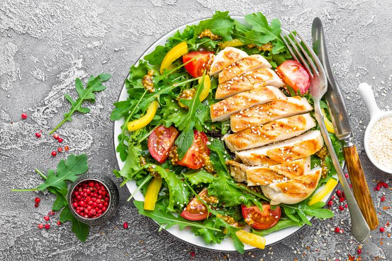 Chicken salad. Meat salad with fresh tomato, sweet pepper, arugula and grilled chicken breast. Chicken fillet with fresh vegetable royalty free stock images