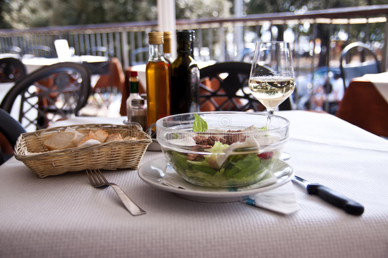 Chicken salad and white wine. Bowl of chicken salad and a glass of white wine in a small restaurant, Trieste, Italy stock image