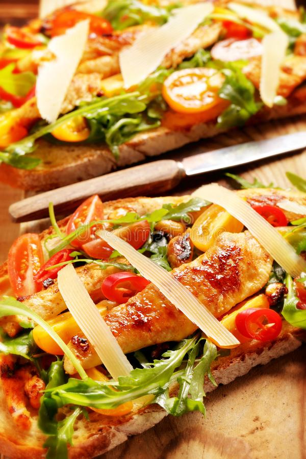 Chicken sandwich on fresh bread with arugula tomato and cheese stock photo