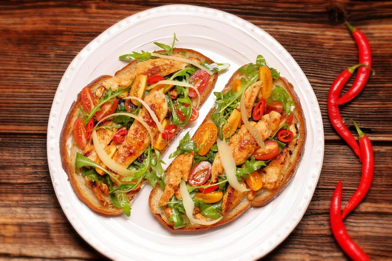 Chicken sandwich on fresh bread with arugula tomato and cheese royalty free stock photography