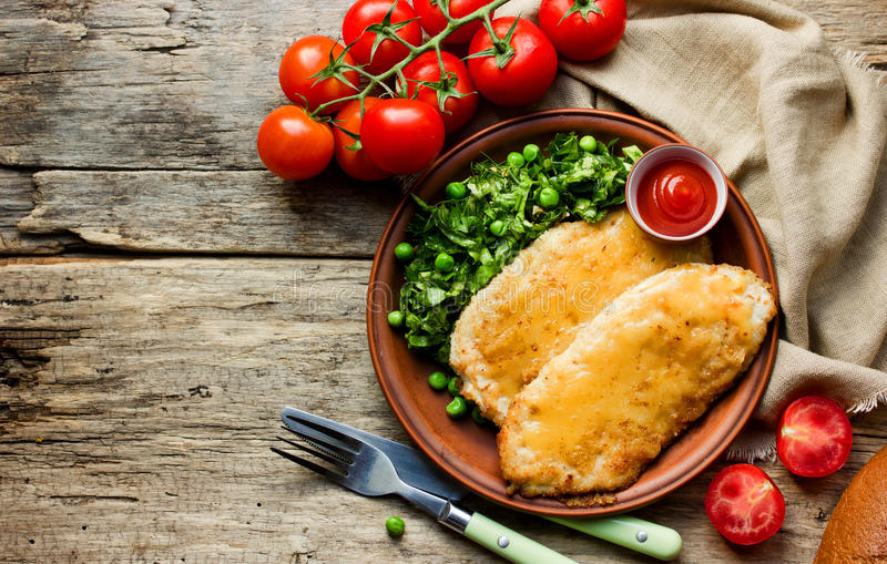 Chicken schnitzel with cheese or cordon bleu with green salad an royalty free stock image