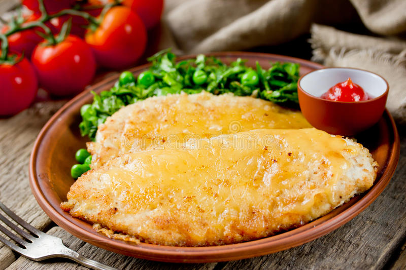 Chicken schnitzel with cheese crust for dinner royalty free stock images
